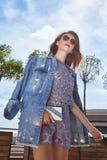 街道样式神色妇女性感的女孩穿戴牛仔布牛仔裤夹克浅黑肤色的男人 免版税库存照片