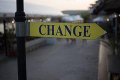 街道牌`在被弄脏的背景的变动` 概念:时间改变,变动方式或地方到交换金钱 免版税库存图片