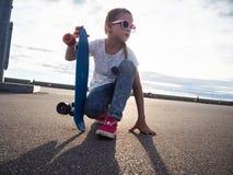 街道生活样式:桃红色太阳镜和桃红色运动鞋的一个女孩坐沥青并且拿着一个蓝色滑板 Portrtet 免版税库存照片