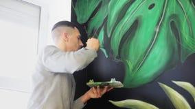 街道画与油漆的艺术家图画在墙壁上 有刷子的男性手 艺术背景黑色概念屏蔽油漆红色地点白色 影视素材