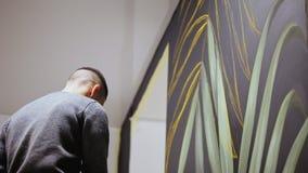 街道画与油漆的艺术家图画在墙壁上 有刷子的男性手 影视素材