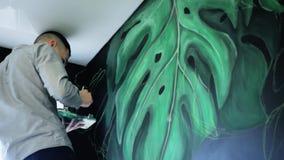 街道画与油漆的艺术家图画在天花板下的墙壁上 有刷子的男性手 艺术背景黑色概念屏蔽油漆红色地点白色 股票录像