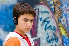 街道画最近的坐的少年墙壁 免版税图库摄影