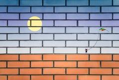 街道画走与在砖墙上的一只风筝的女孩 免版税库存照片