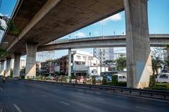 街道的交通在高速公路下的有房子和天空蔚蓝背景的 免版税库存图片