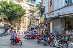 街道的地方日常生活在河内,越南 人们能看见食用他们的在街道旁边的食物 免版税库存照片
