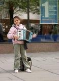 街道的女孩与手风琴 免版税库存图片