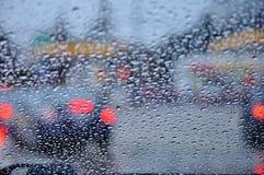 街道的看法通过一块湿挡风玻璃 免版税库存图片