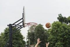 街道篮球比赛 篮球盾、篮子和球在天空,街道背景在夏天 篮球的手 免版税库存图片