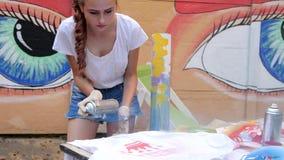 街道绘画,有在手中喷漆的女孩,青年期与湿剂油漆在街道画背景在慢动作的 影视素材
