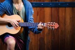 街道艺术家使用与他的在一个老门前面的吉他 免版税库存图片