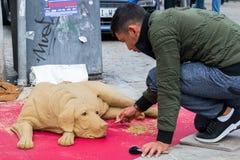 街道艺术家在步行区域塑造与沙子的一条狗在雷根斯堡,德国 免版税库存照片