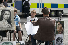 街道艺术家在莱斯特广场绘男孩的画象 免版税库存照片