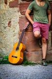 街道艺术家站立与他的在老墙壁上的吉他 免版税库存照片