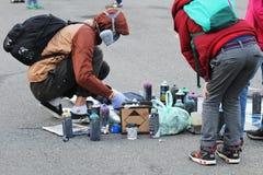 街道画艺术家绘画 街道艺术家绘画五颜六色的街道画沥青 都市人执行 现代美术的概念 小男孩 免版税库存照片