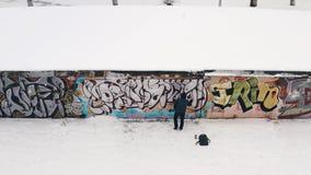 街道艺术家鸟瞰图喷洒在墙壁上的黑暗的衣裳的一张街道画在冬天 r r 免版税库存图片