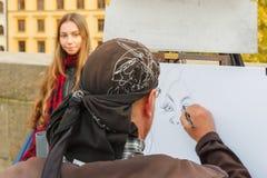 街道艺术家绘一个美丽的女孩的画象讽刺画 库存图片