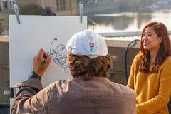 街道艺术家绘一个美丽的女孩的画象讽刺画 免版税库存图片
