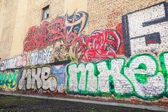 街道艺术,有街道画文本的黄色砖墙 库存图片