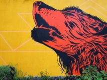 街道艺术:红狼在黄色墙壁前面嗥叫 免版税库存图片