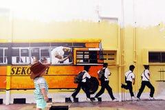 街道艺术-有学生的校车 免版税库存图片