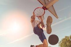 街道蓝球运动员执行的力量贫民窟扣篮 库存图片