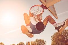 街道蓝球运动员执行的力量贫民窟扣篮 免版税库存照片