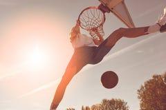 街道蓝球运动员执行的力量贫民窟扣篮 库存照片