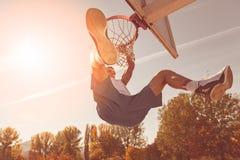 街道蓝球运动员执行的力量贫民窟扣篮 免版税库存图片