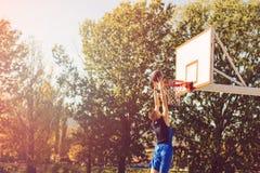 街道蓝球运动员执行的力量贫民窟扣篮 免版税图库摄影