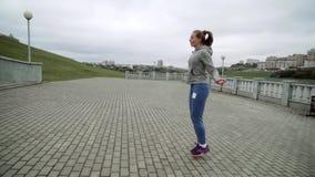 街道跳绳的逗人喜爱的金发碧眼的女人 女孩参与体育运动 影视素材