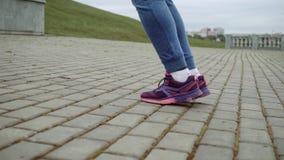 街道跳绳的逗人喜爱的金发碧眼的女人 女孩参与在新鲜空气的体育 跳跃与绳索 腿关闭 影视素材