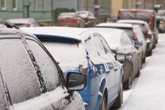 街道都市场面有停放的积雪的汽车的 库存照片