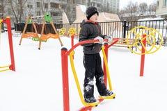 街道锻炼设备在冬天、户外运动健身和体型 男孩在做锻炼锻炼的体育操场 图库摄影