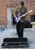 街道音乐家弹吉他室外在克拉科夫,波兰 免版税库存照片