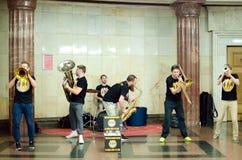 街道音乐家弹奏在地铁车站的乐器 免版税库存照片
