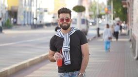 街道食物和城市生活的概念 拿着有饮料汁液圆滑的人或柠檬水的年轻微笑的有胡子的人一个杯子 影视素材