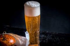 街道食物 与杯的一个大汉堡低度黄啤酒 在一个木背景 库存照片