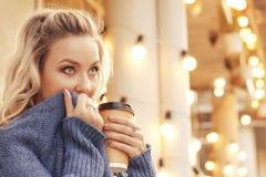 街道饮用的早晨咖啡的快乐的妇女在阳光光 免版税库存照片