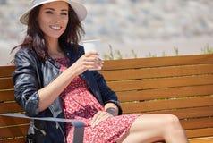 街道饮用的早晨咖啡的快乐的妇女在阳光光 图库摄影