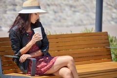 街道饮用的早晨咖啡的快乐的妇女在阳光光 库存图片