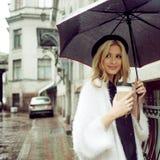 街道饮用的早晨咖啡的快乐的妇女 免版税库存图片