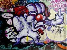 街道画-一张被破坏的街道画的段在都市墙壁上的 库存照片