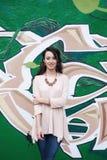 街道画背景的典雅的女孩 免版税库存照片