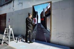 街道画艺术家油漆在墙壁上的一张壁画 免版税库存图片