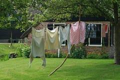 洗衣店烘干在靠近农舍之外的一条线 免版税库存照片