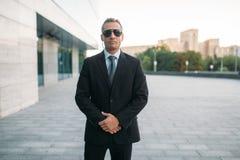 衣服、听筒和太阳镜的男性保镖 免版税库存图片