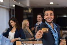 衣服举行信用卡愉快微笑的拉丁人,当购物在典雅的男服商店时 免版税库存照片
