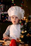 衣服厨师的女孩滚动与滚针的面团 免版税库存图片