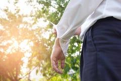 衣服和一件白色衬衣的商人卷起他的在n的袖子 免版税库存图片